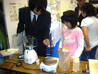 小学生インターシップの様子:研究開発部員とはがきを作成